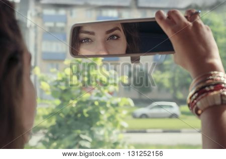 Woman Looking At Her Reflection In The Rearview