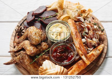 Beer snacks mix on wooden board with two sauces top view. Flat lay of closeup tasty set of grilled chicken wings, chips, meat and cheese on white wooden background