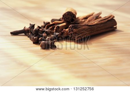 clove spice cinnamon sticks on a wooden board background