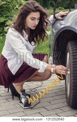 Woman Pumps Up Her Car Tire