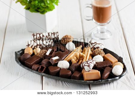 Delicious plate with different sweets on white wooden table with cappuccino. Chocolate candies and cookies on black plate. Close-up of chocolate candies set, front view, focus on foreground.
