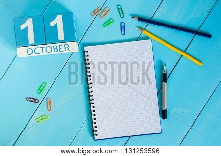 October 11th. Image of October 11 wooden color calendar on blue background. Autumn day. Empty space for text.