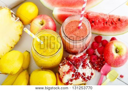 Fresh organic red and yellow smoothie with apple, watermelon, pomegranate, raspberry, pineapple, banana and mango. Healthy, vegan drinks.