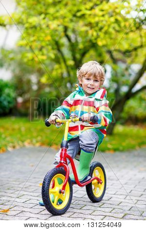 Cute blond kid boy driving on bicycle on rainy summer or autumn day outdoors. Preschool child  in colorful rain jacket and boots having fun in park.
