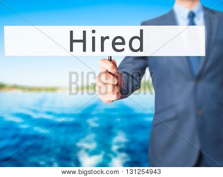 Hired - Businessman Hand Holding Sign