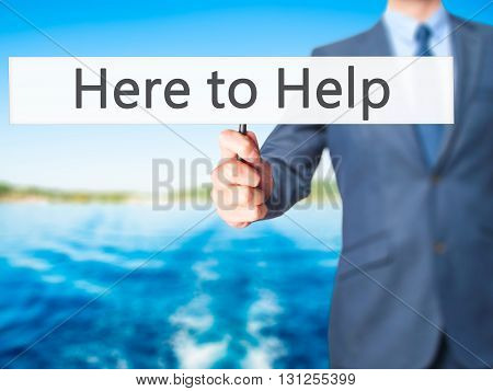 Here To Help - Businessman Hand Holding Sign