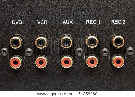 Sockets of various inputs on an black metal panel. It is part of the rear panel of the amplifier.
