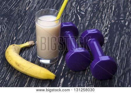 banana, juice and dumbbells on white wooden desk