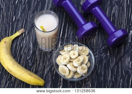 Banana juice, bananas and two dumbbells on wooden desk