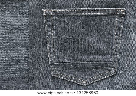 fragment of trousers from jeans material or jeans clothes with the big sewn pocket closeup for the textile textured background of gray color