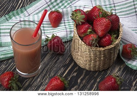 Juice and strawberries in a basket on the wooden desk
