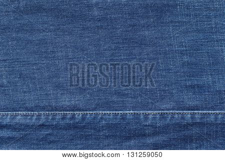 denim or rough cotton fabric or jeans material with the stitched seam for the textile textured background of blue color