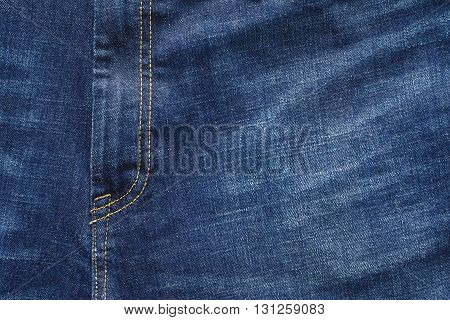 fragment closeup of trousers from jeans material or jeans clothes with a codpiece for the textile textured background of blue color