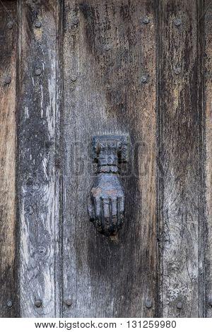 Iron door knocker in the form of human hand on old wooden door