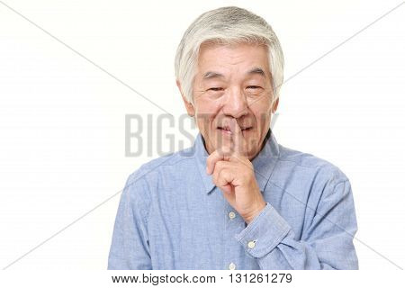 portrait of senior Japanese man whith silence gestures on white background