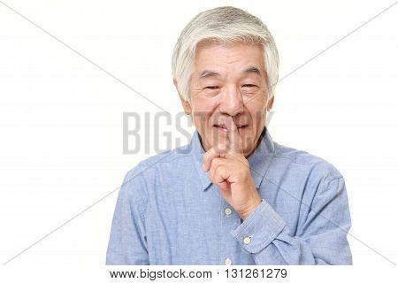 portrait of senior Japanese man whith silence gestures on white background