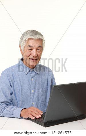 portrait of senior Japanese  man using laptop computer on white background