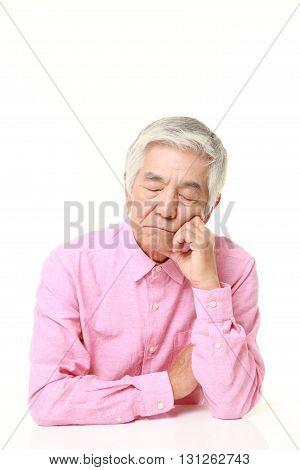 portrait of senior Japanese man sleeping on the table on white background