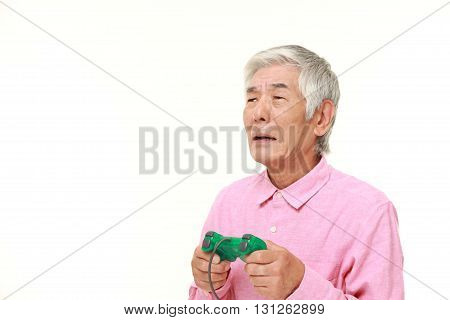 portrait of senior Japanese man losing playing video game on white background