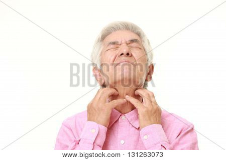 portrait of senior Japanese man scratching his neck on white background