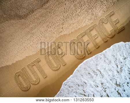 Out of Office written on the beach