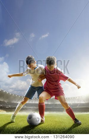 Children are playing soccer on grand arena in sunlight