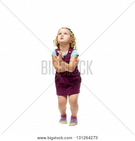 Young little girl with curly hair and crossed arms in purple dress jumping over isolated white background