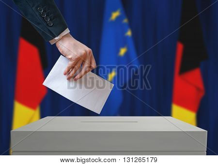 Election In Germany. Voter Holds Envelope In Hand Above Vote Bal