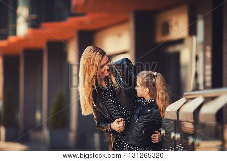 woman and little girl smiling in the city