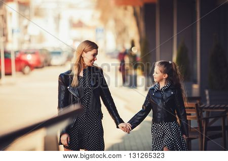 Happy family mother and child little daughter walking and playing in city