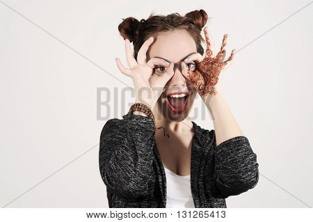 Young funny and cute hipster woman is joking and making spectacles from her hands.