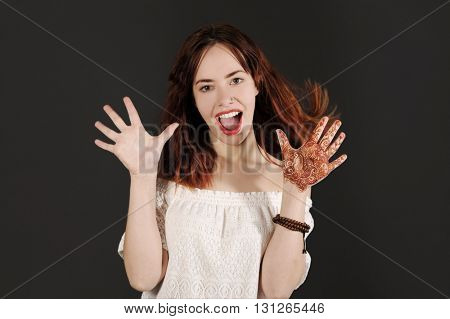 Young and happy hipster woman screaming enthusiastically. studio shot with dark background.