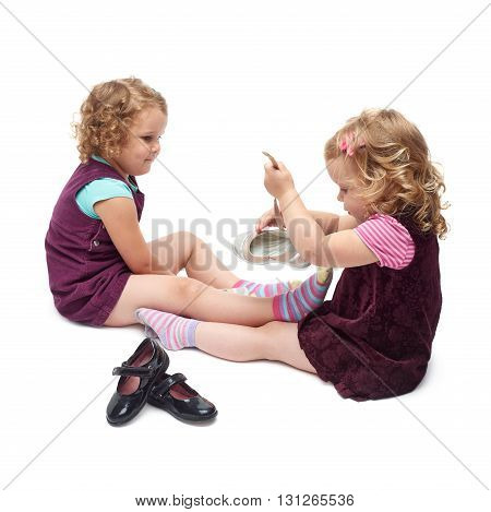 Couple of young little girls sisters with curly hair in purple dress sitting and putting shoes over isolated white background