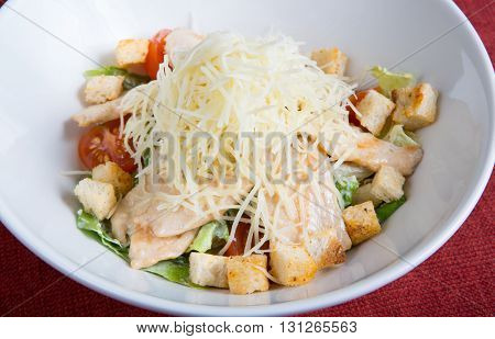 Fresh cesar salad served with cheese and croutons