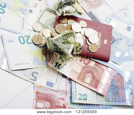 Travel on vacation lifestyle concept: cash money on table in mess with passport and change isolated