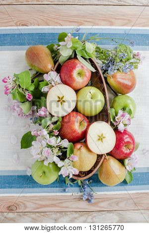 Apple and pears in spring composition with flower on the wood table with linen tablecloth