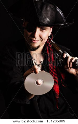 Photo of a smiling man in a pirate costume holding out compact disc.