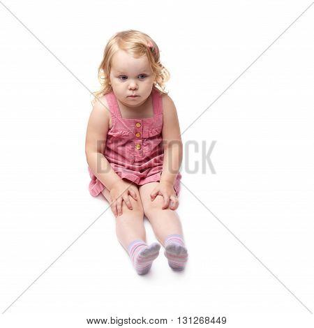 Young little girl with curly hair in pink dress sitting over isolated white background