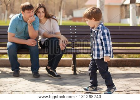 Young parents and little son in the park. Father and mother sitting on a bench in the park and looking at his son.