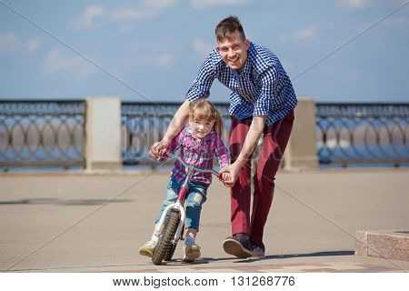 Father Teaching Daughter To Ride Bike