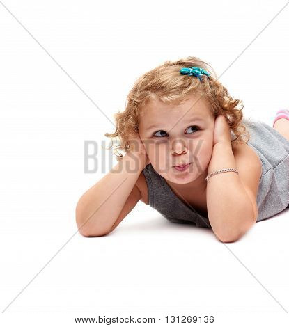 Young little girl with curly hair in gray dress lying over isolated white background