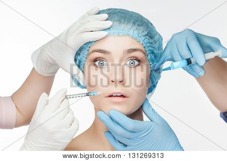 Attractive frightened woman at plastic surgery with syringe in her face on white background