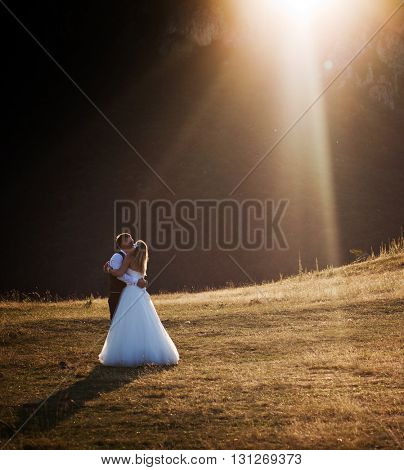Romantic wedding couple in beautiful scenery at sunset