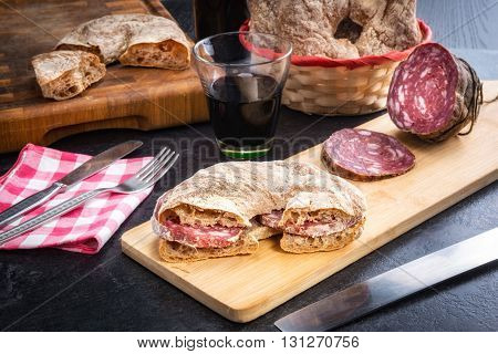 Bread of Valtellina cut and filled with Italian salami served on a wooden board accompanied by red wine
