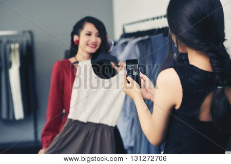 Woman photographing her friend trying on dress