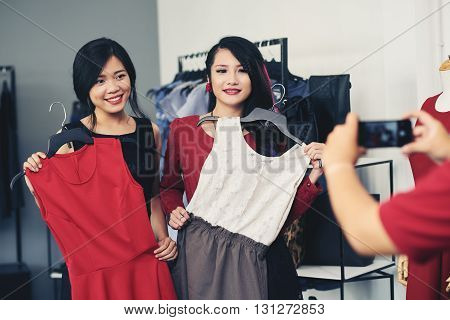 Two Vietnamese female friends showing dresses they have chosen