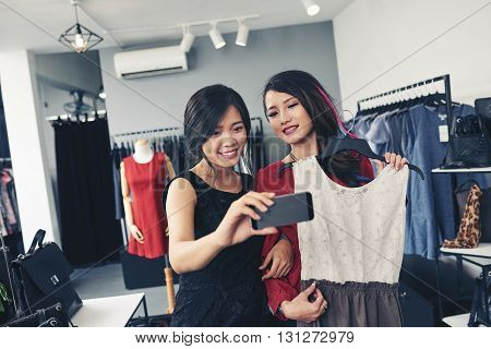 Vietnamese female friends taking selfie in boutique