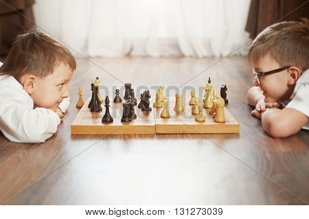 Two serious boy playing chess, studio, background