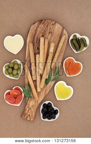 Crudites selection with bread sticks, mayo and chili dips, olives, oil, gherkins and tomatoes on an olive wood   board.