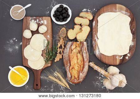 Baking ingredients with rustic bread loaf, dough, yeast, black olives, olive oil, garlic, herb and rye grain in a love spoon on maple wood over grey.